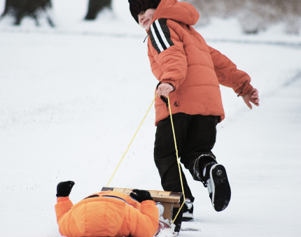 Child Pulling brother on a sled