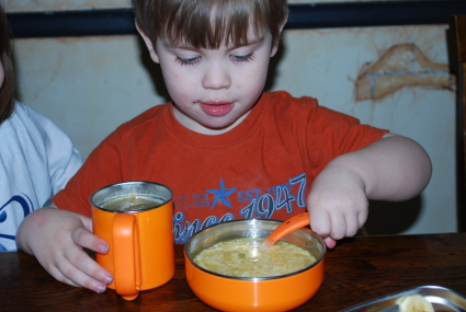 Toddler eating out of ThinkBaby bowl and cup